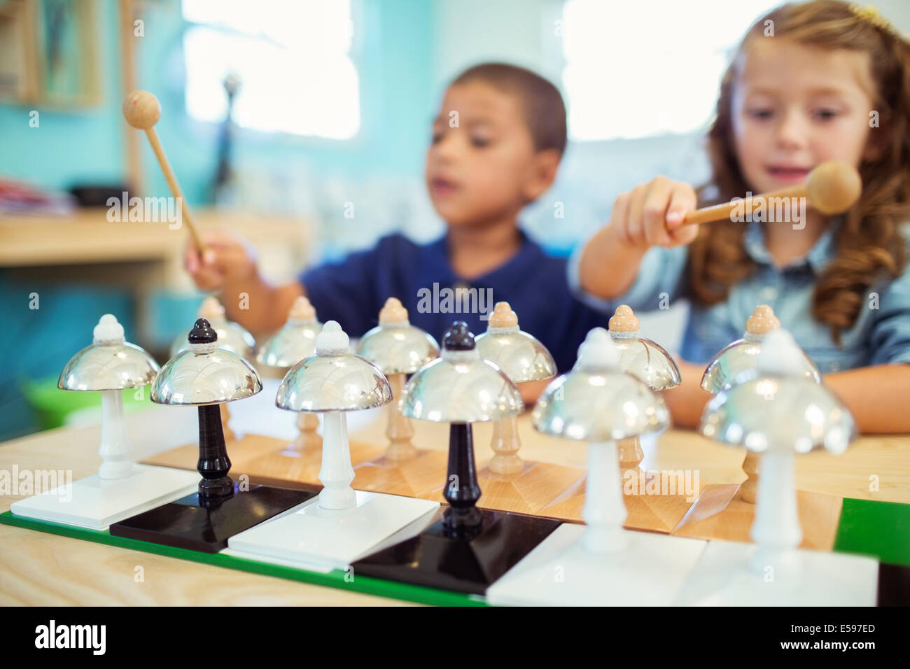 Students playing bells in class - Stock Image