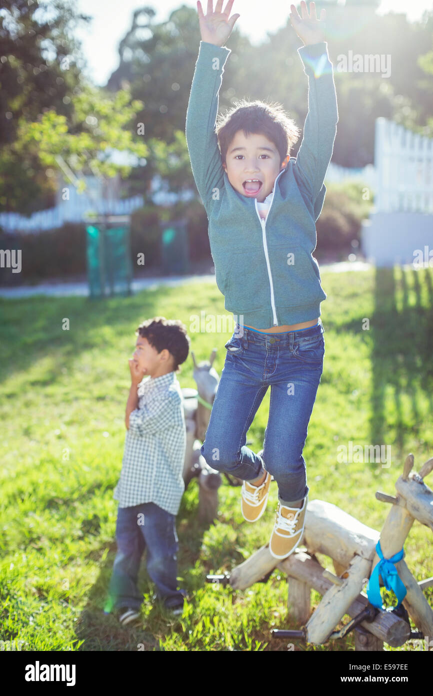 Boy jumping for joy outdoors - Stock Image