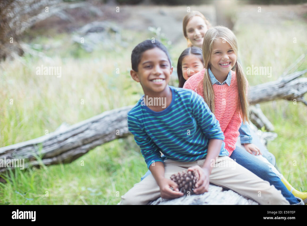 Children sitting on log in forest - Stock Image