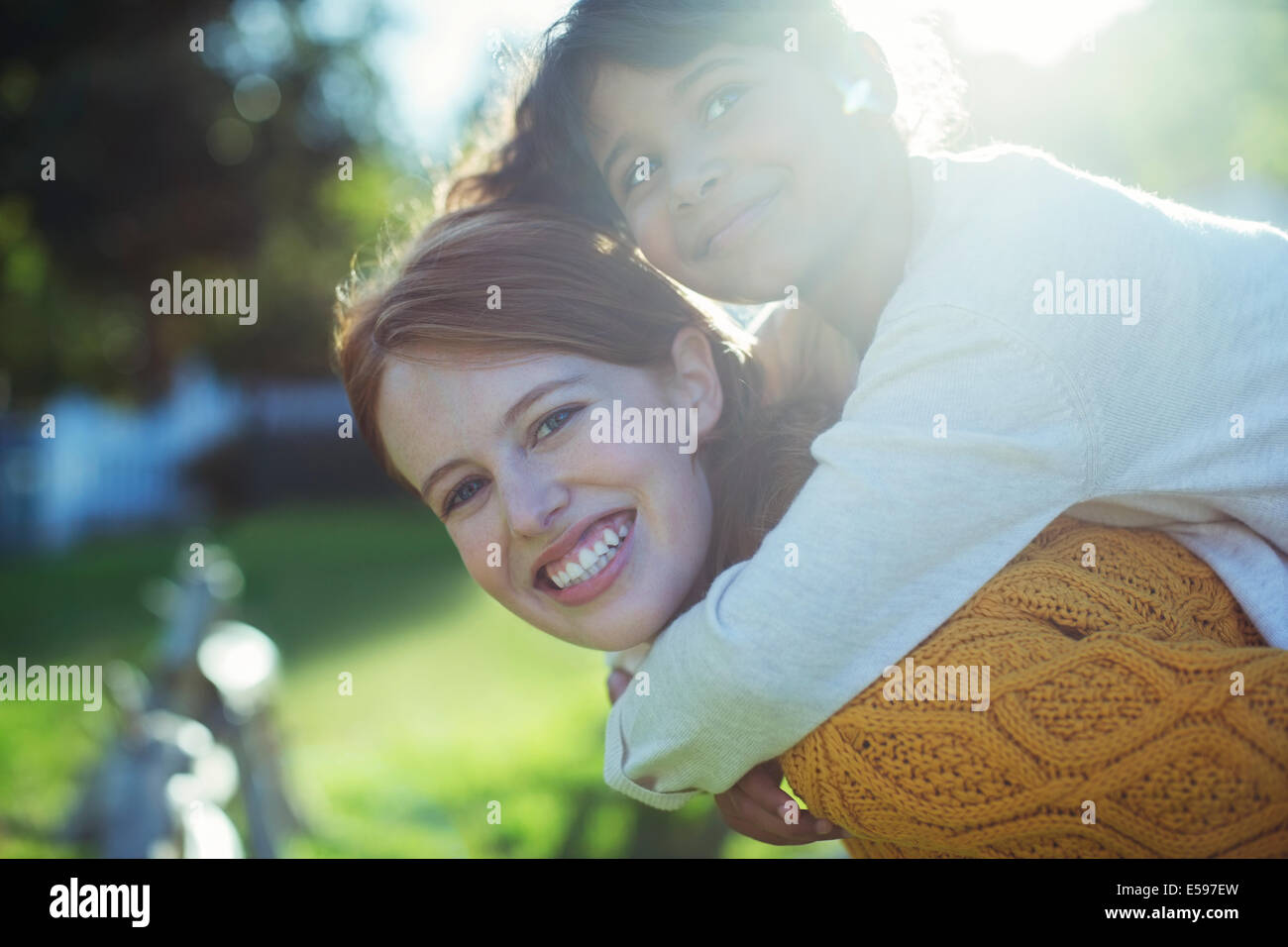 Mother carrying daughter on shoulders - Stock Image