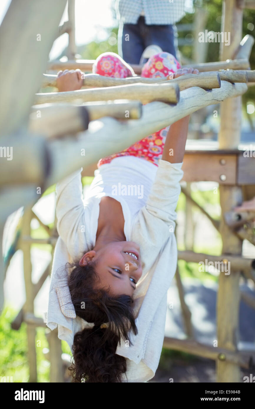 Girl climbing on monkey bars on playground Stock Photo