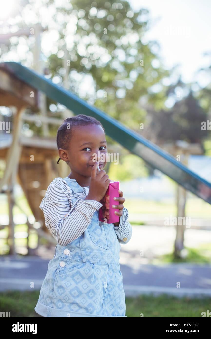Girl drinking juice box at playground - Stock Image