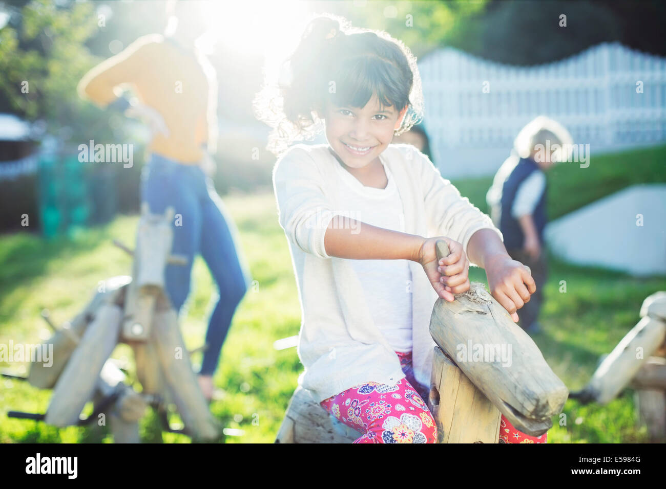 Girl smiling on rocking horse in playground - Stock Image