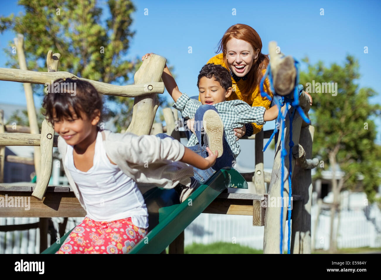 Teacher and students playing on playground - Stock Image
