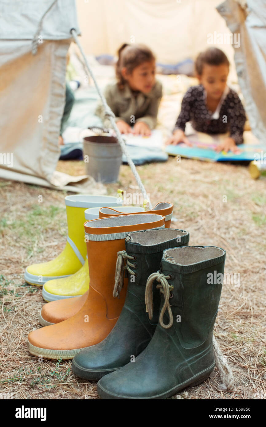 Rainboots lined up outside tent at campsite - Stock Image