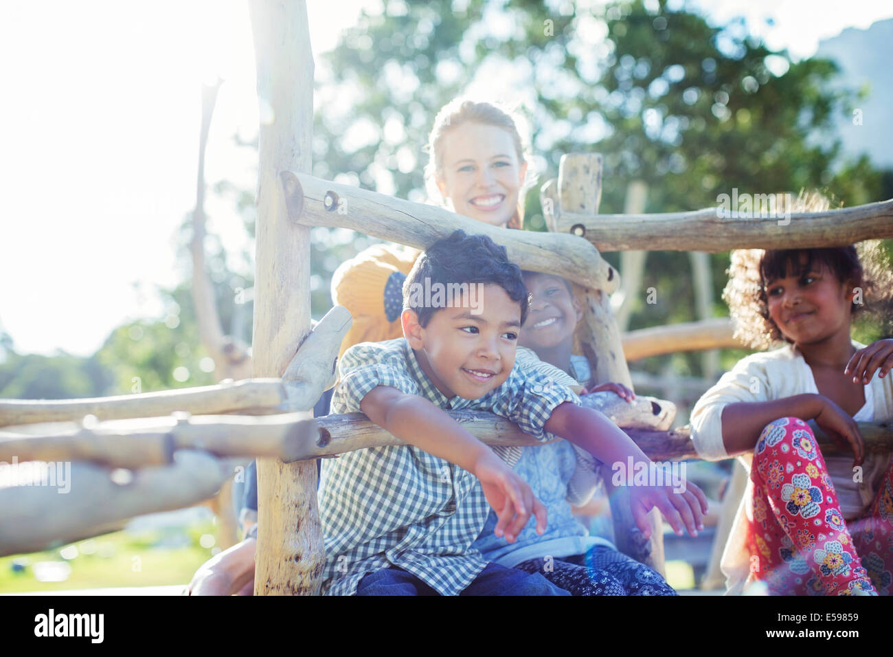 Teacher and students playing on play structure Stock Photo