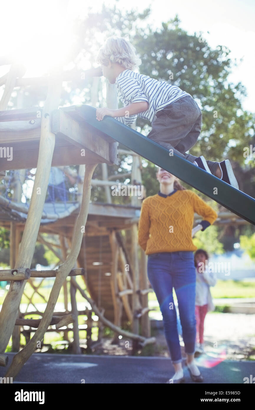Teacher watching student play on play structure - Stock Image