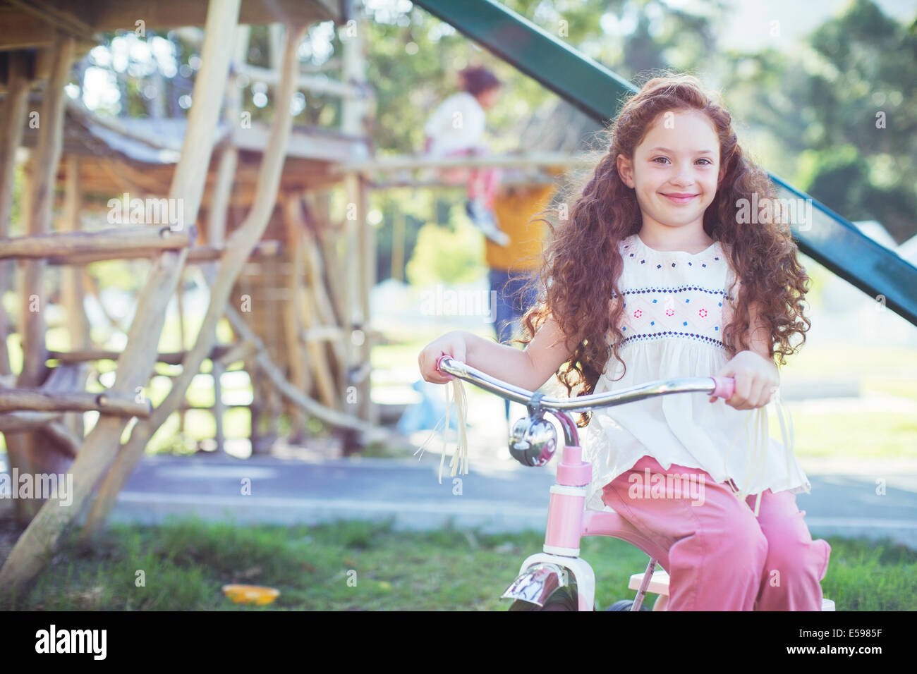 Smiling girl sitting on bicycle at playground - Stock Image