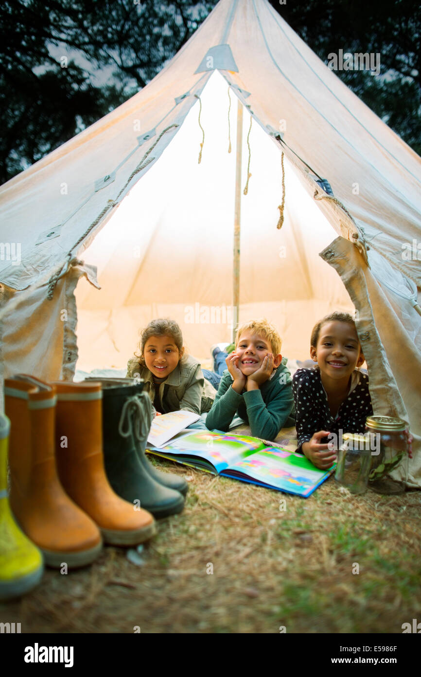 Children smiling in tent at campsite - Stock Image