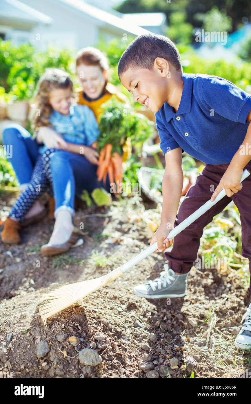 Boy turning over soil in garden - Stock Image