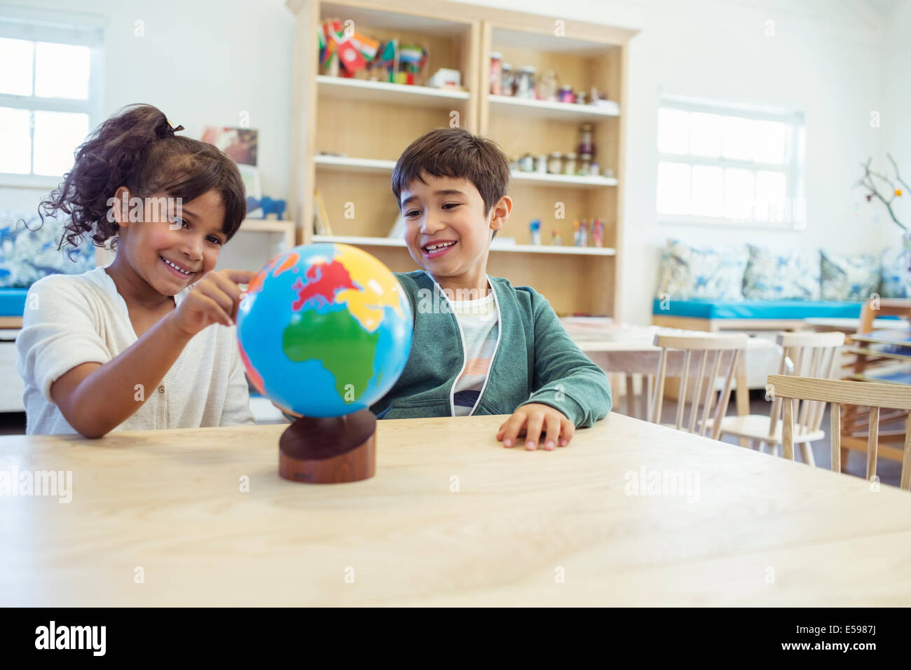 Students examining globe in classroom - Stock Image