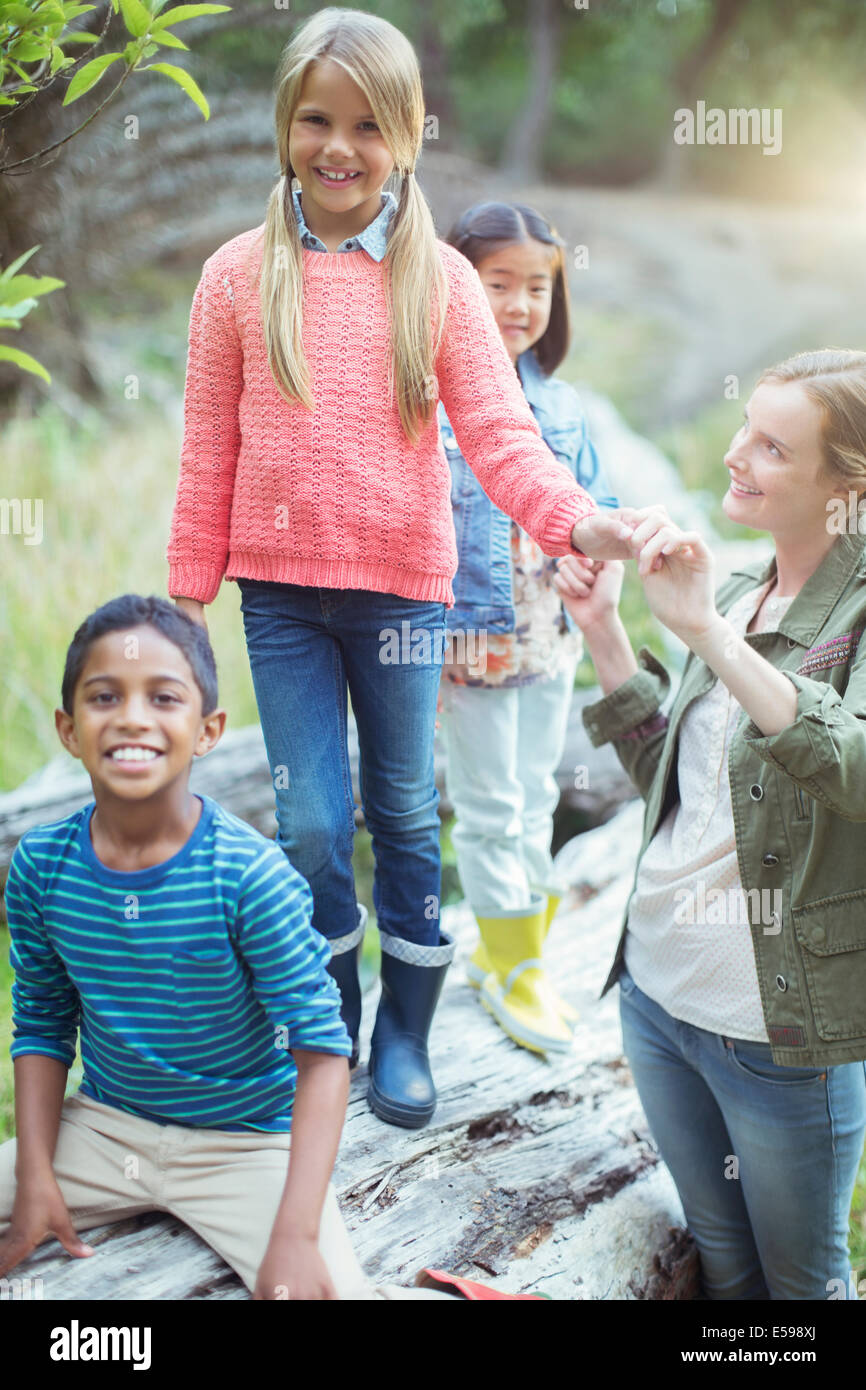 Students and teacher climbing on log - Stock Image