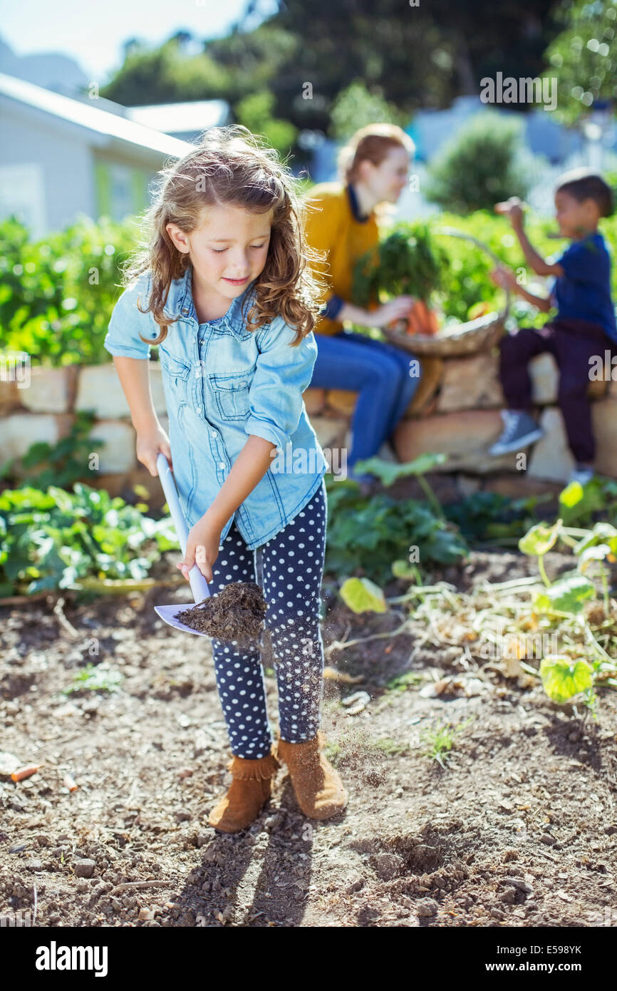Girl shoveling dirt in garden - Stock Image