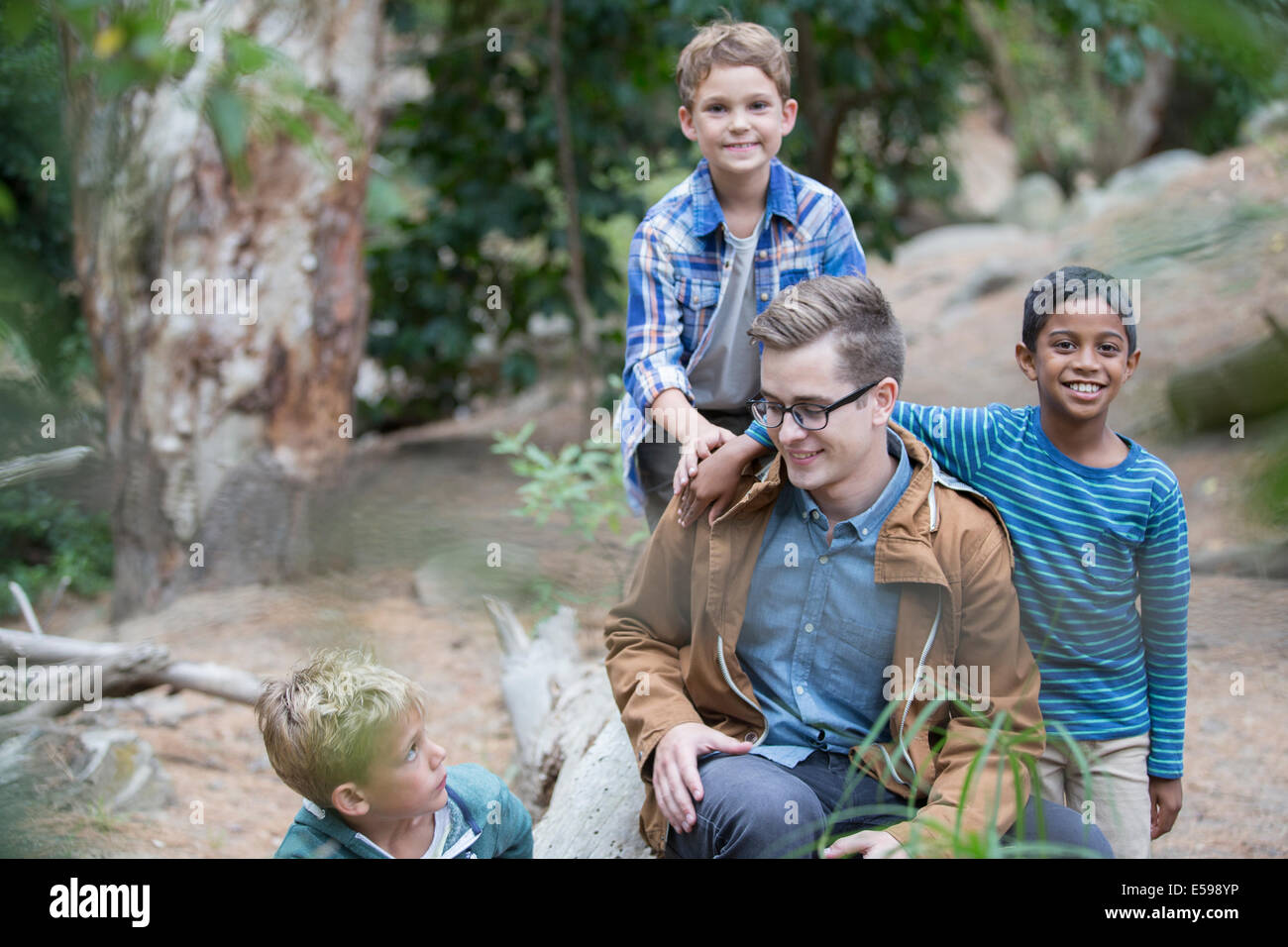 Students and teacher playing in forest - Stock Image