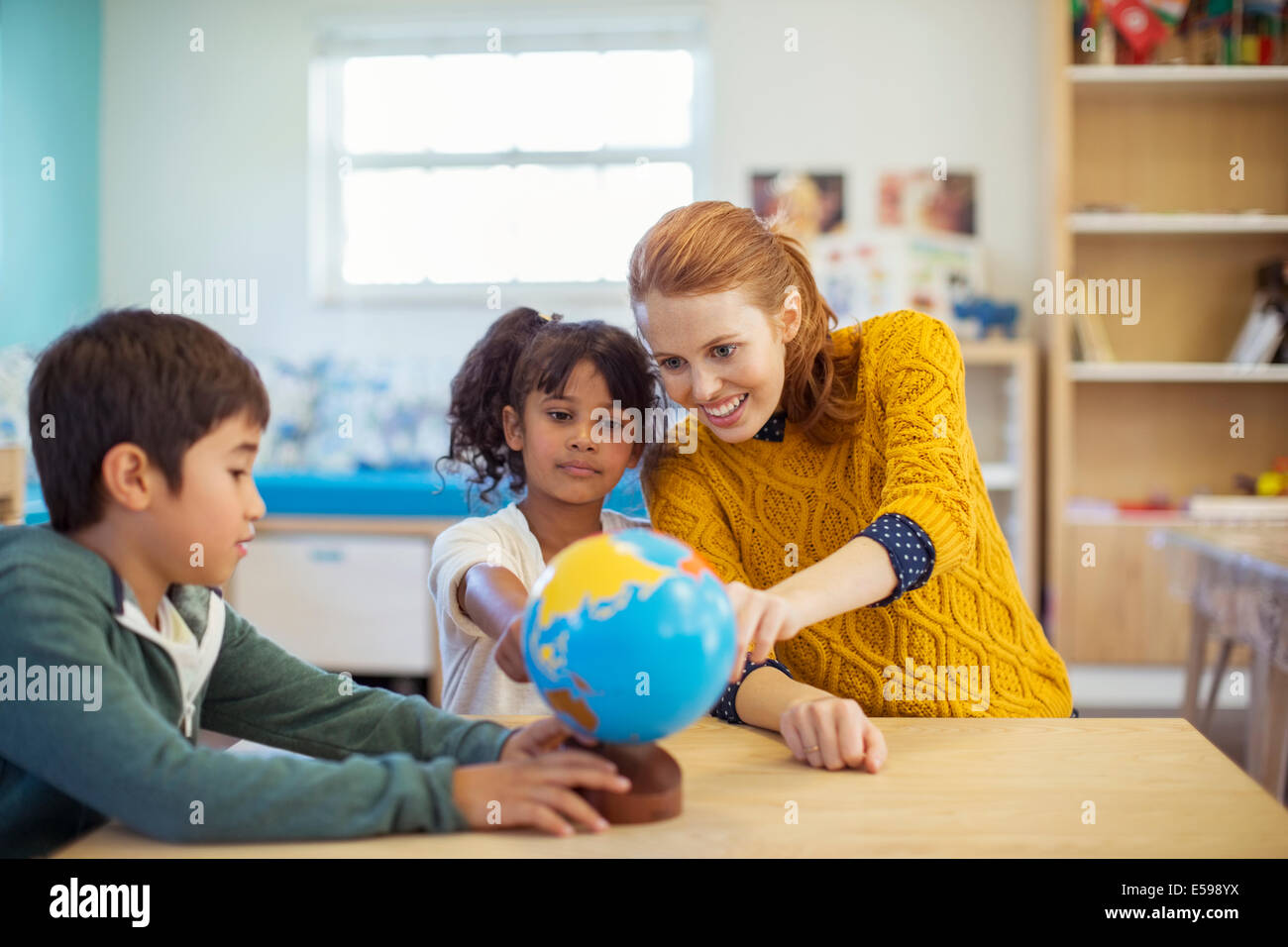 Students and teacher examining globe in classroom - Stock Image