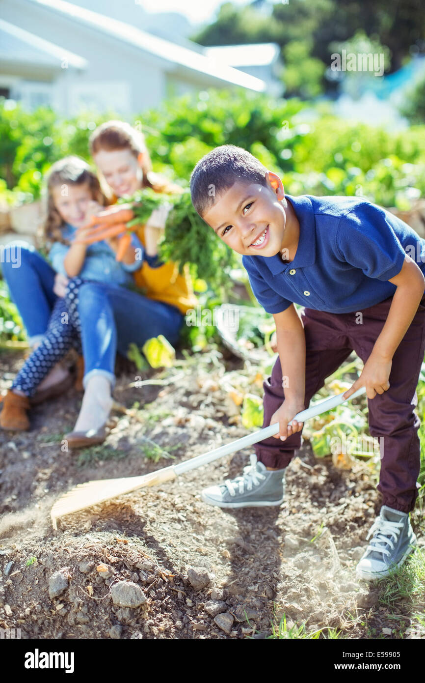 Boy turning over dirt in garden - Stock Image