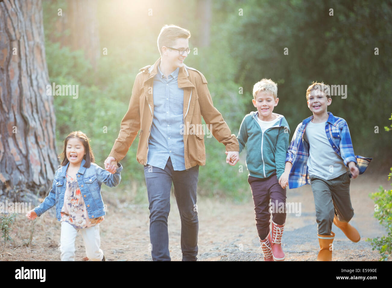 Students and teacher walking in forest - Stock Image