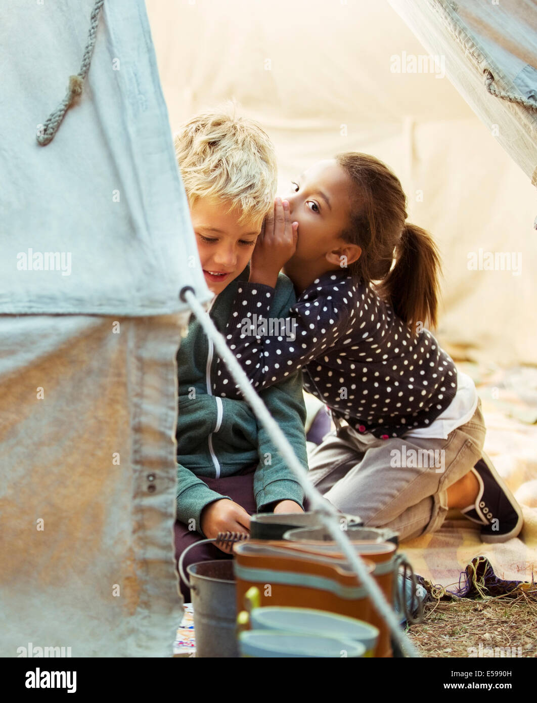 Children whispering in tent at campsite - Stock Image