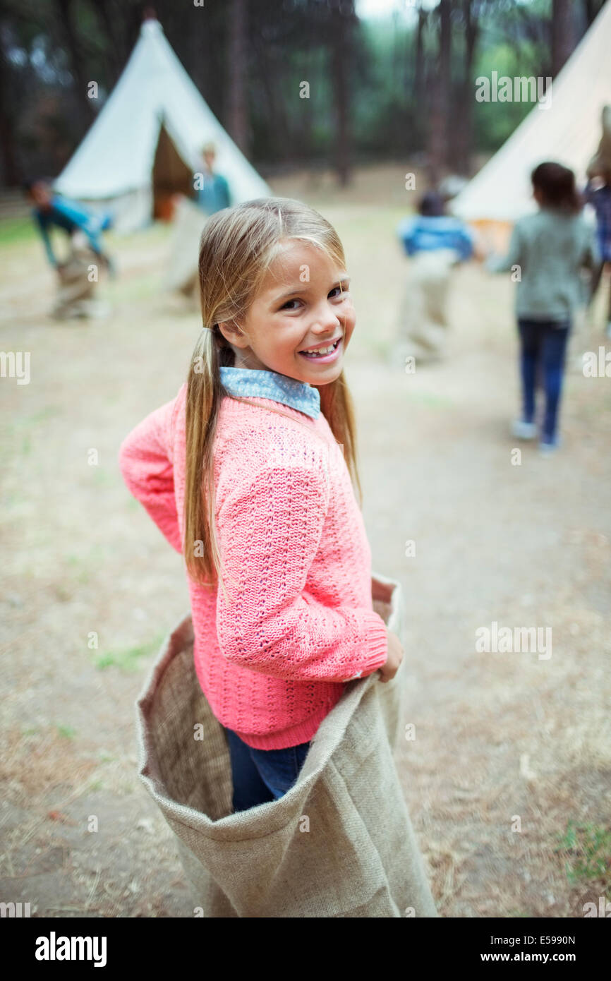 Girl smiling in sack at campsite - Stock Image