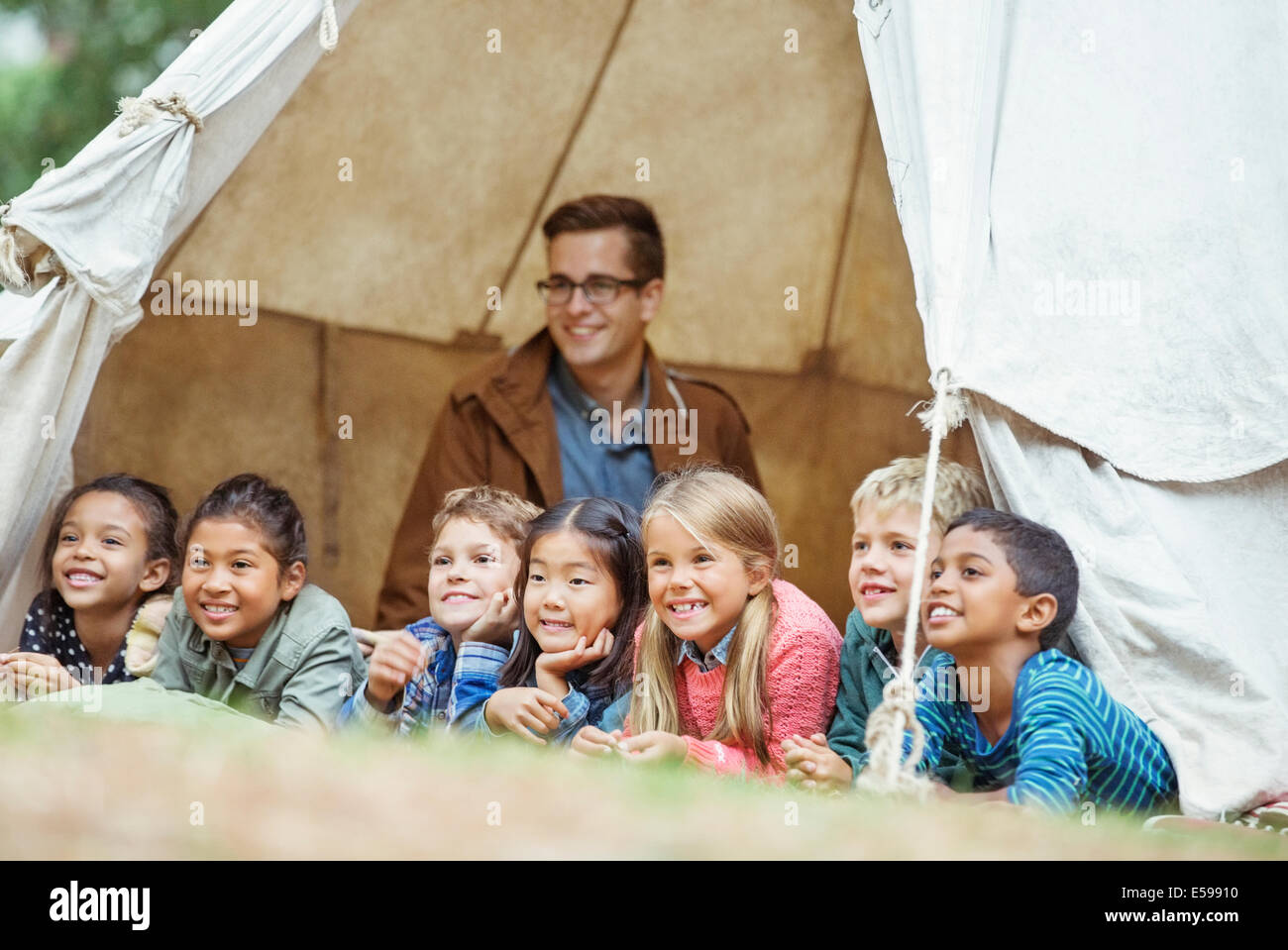 Students and teacher smiling in tent at campsite - Stock Image