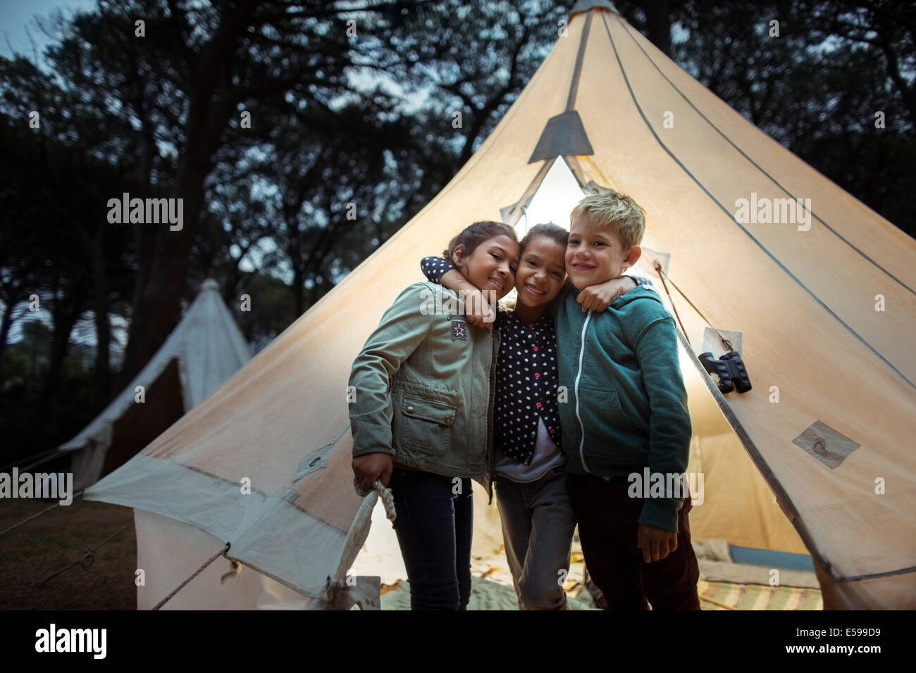 Children hugging by teepee at campsite - Stock Image