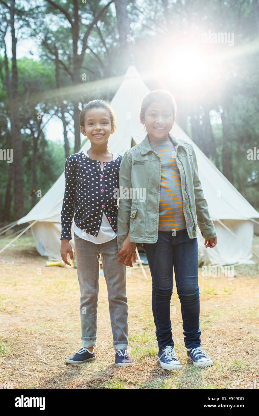 Girls smiling by teepee at campsite - Stock Image