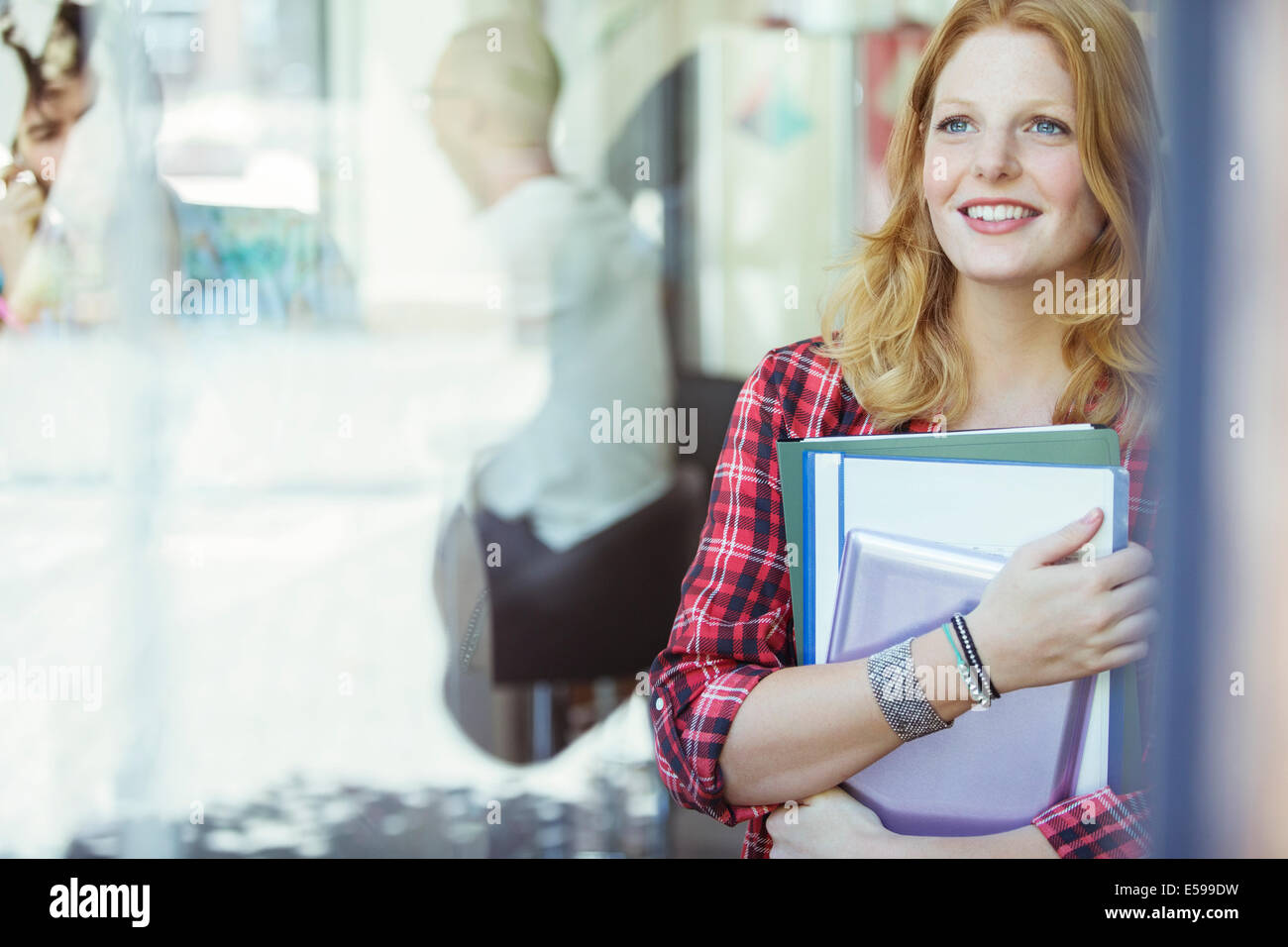 Woman carrying binders outdoors - Stock Image