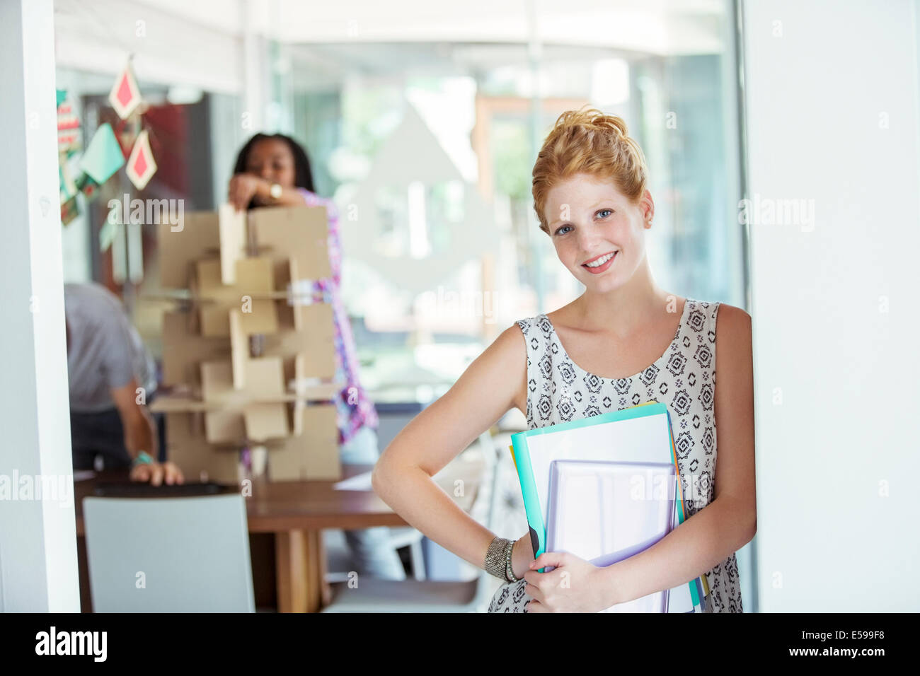 Businesswoman carrying binders in office - Stock Image