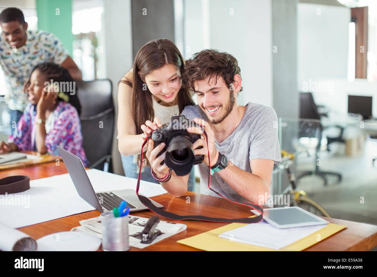 People reviewing photos together in office - Stock Image