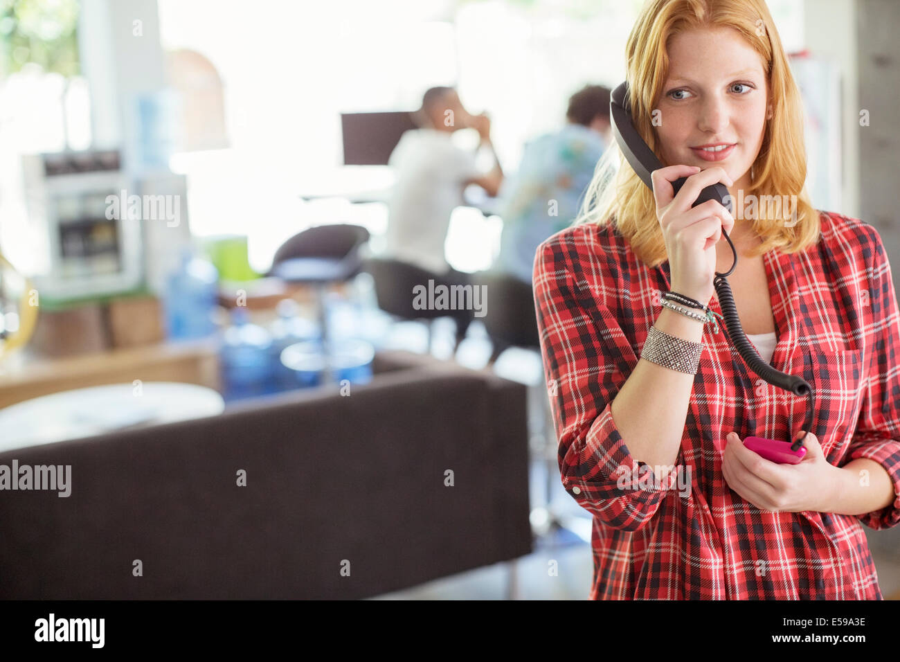 Woman talking on phone in office - Stock Image