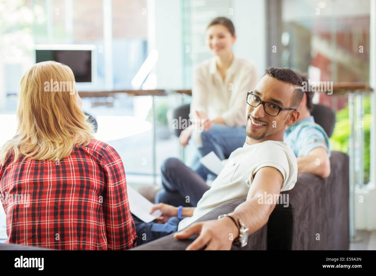 People smiling in office lobby area - Stock Image