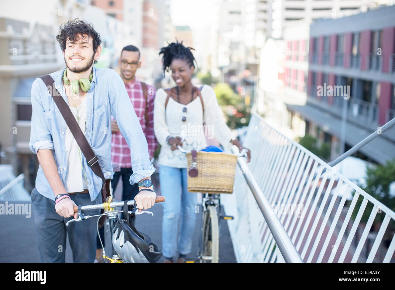 Friends pushing bicycles on city street - Stock Image
