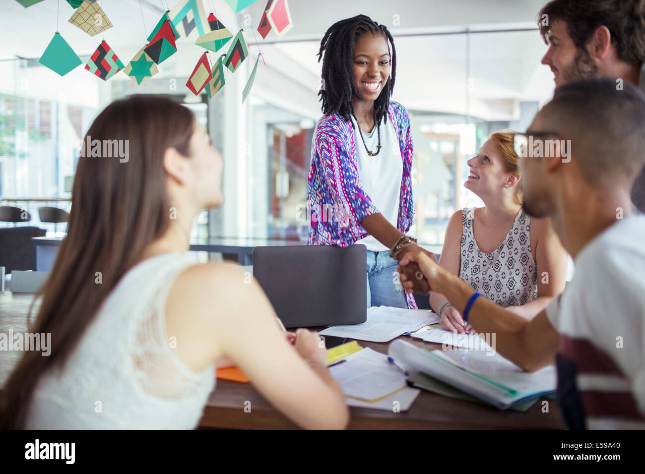 People shaking hands in meeting - Stock Image