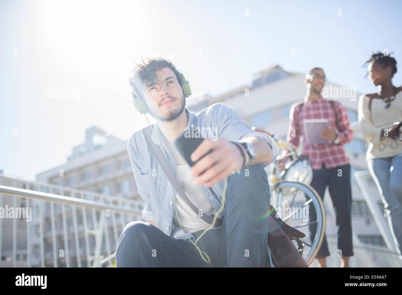 Man listening to headphones on city street - Stock Image