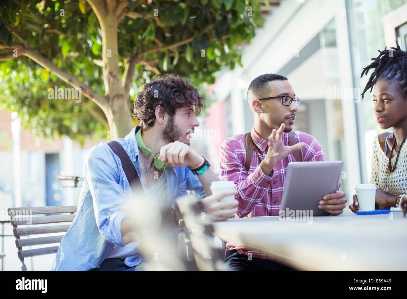 Friends talking at sidewalk cafe - Stock Image