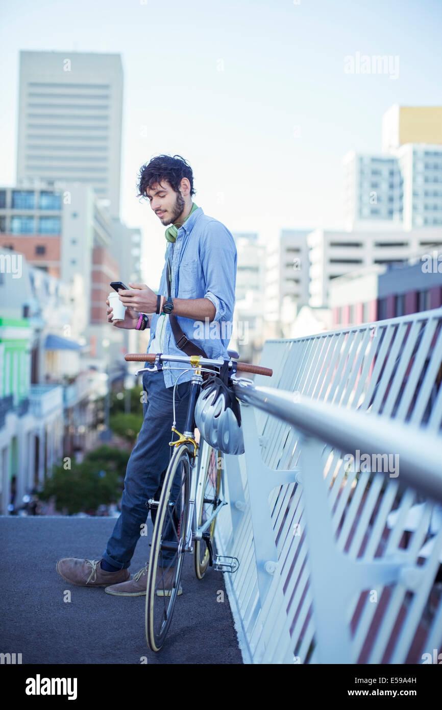 Man using cell phone on city street Stock Photo
