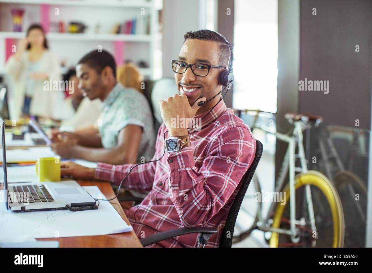 Man smiling at desk in office - Stock Image
