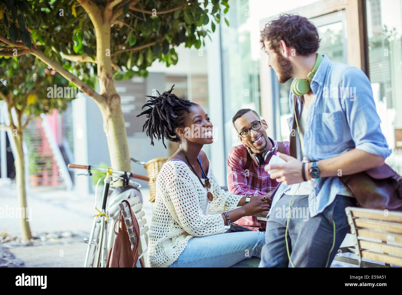 Friends talking on city street - Stock Image