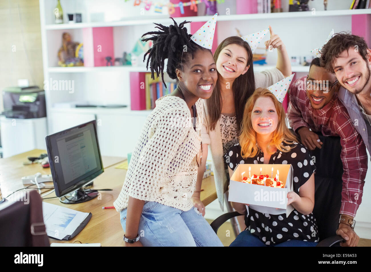 People celebrating birthday in office - Stock Image