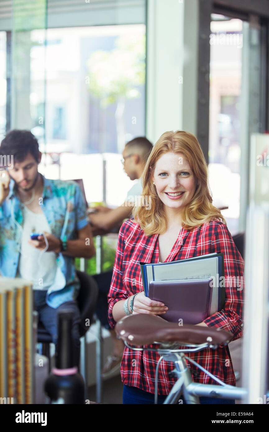 Woman carrying folders in cafe - Stock Image