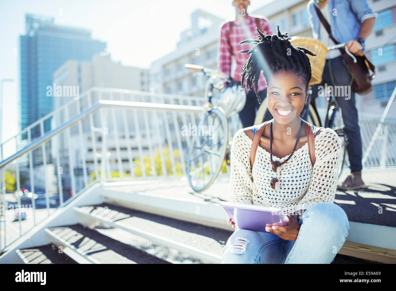 Woman using digital tablet on city street - Stock Image