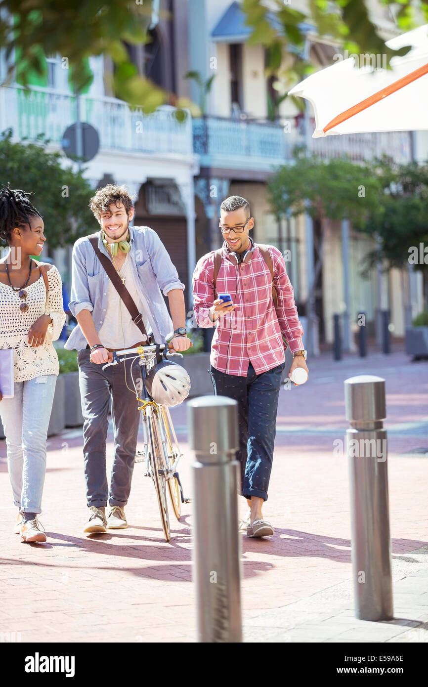 Friends walking together on city street - Stock Image
