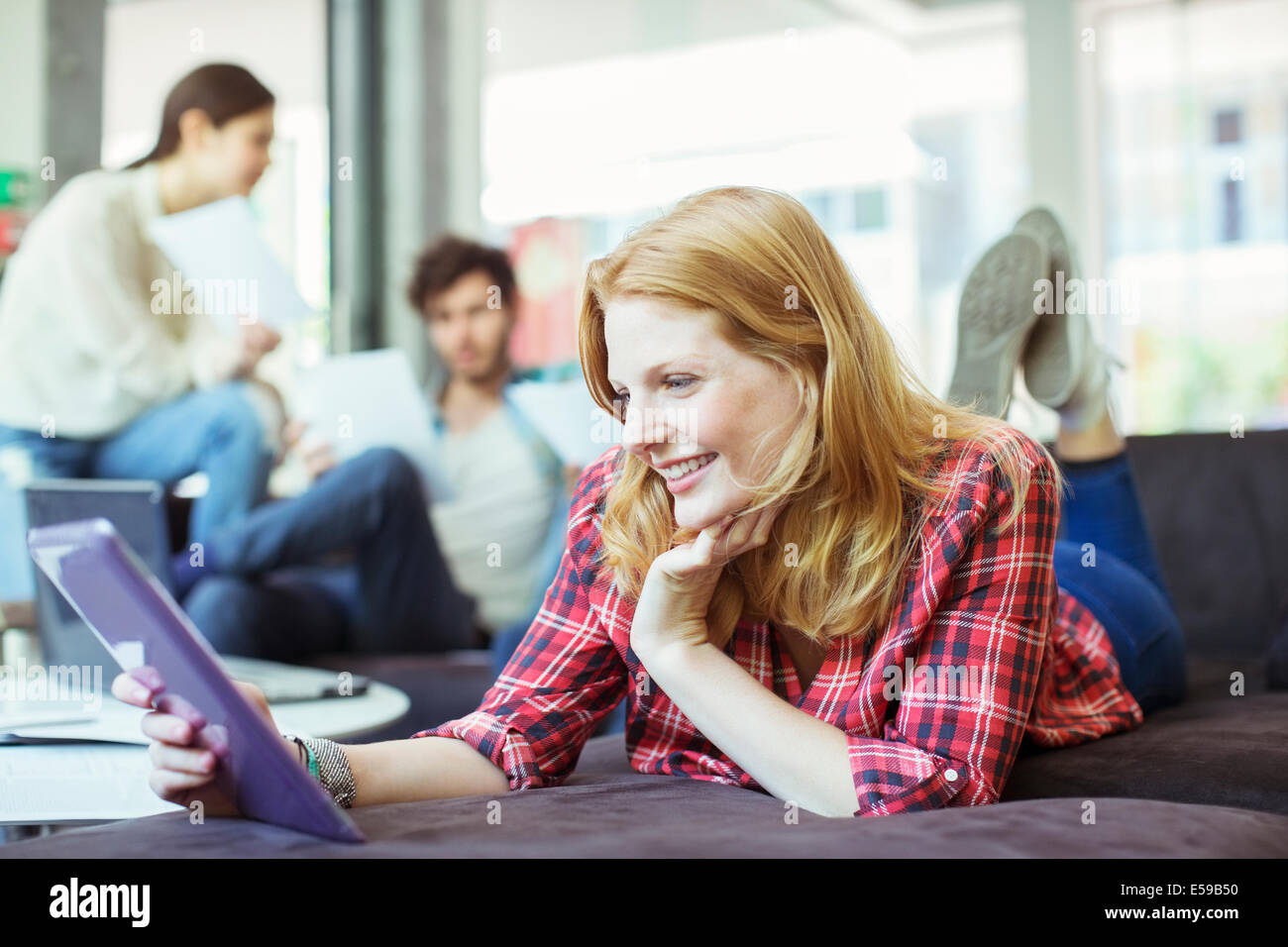 People using digital tablet in office - Stock Image