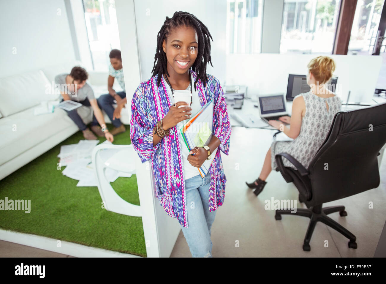 Woman drinking coffee in office - Stock Image