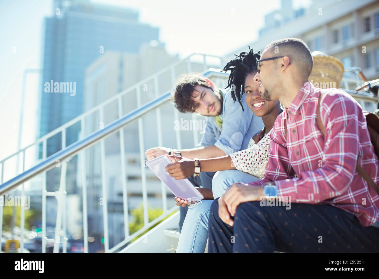 Friends sitting on city steps - Stock Image