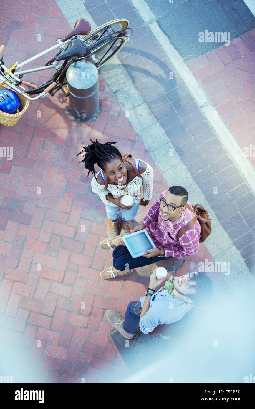 Friends using digital tablet on city street - Stock Image