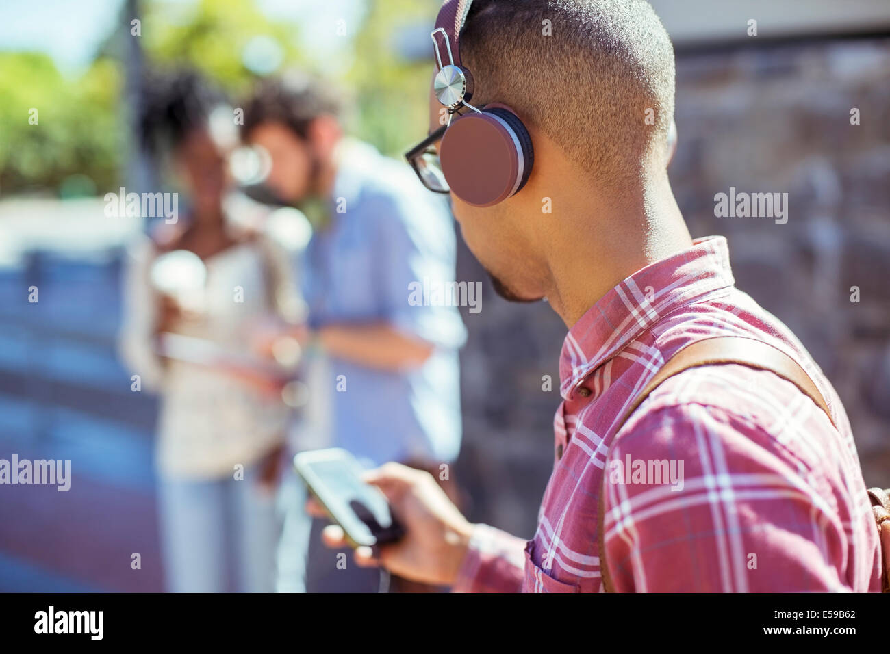 Man listening to mp3 player outdoors - Stock Image