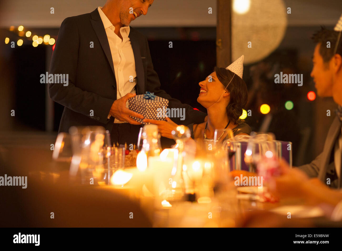 Man giving wife gift at birthday party - Stock Image