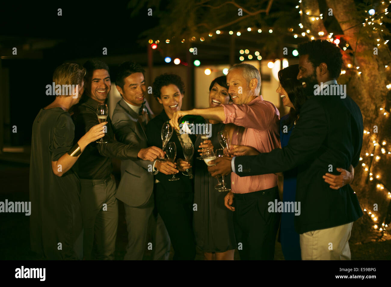 Friends celebrating with champagne at party - Stock Image