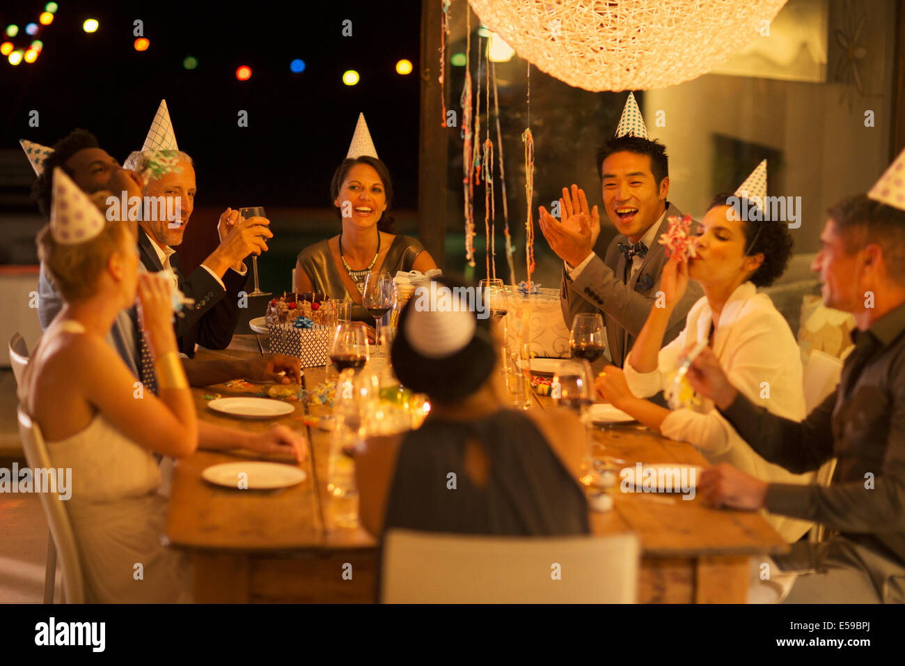 Friends cheering at birthday party - Stock Image